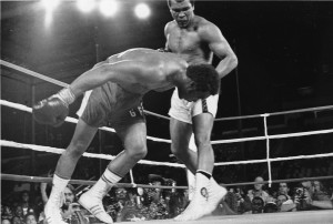 Challenger Muhammad Ali watches as defending world champion George Foreman goes down to the canvas in the eighth round of their WBA/WBC championship match in Kinshasa, Zaire, on Oct. 30, 1974. Foreman was counted out by the referee and Ali regained the world heavyweight crown by KO in the bout dubbed 'Rumble in the Jungle.' (AP Photo)